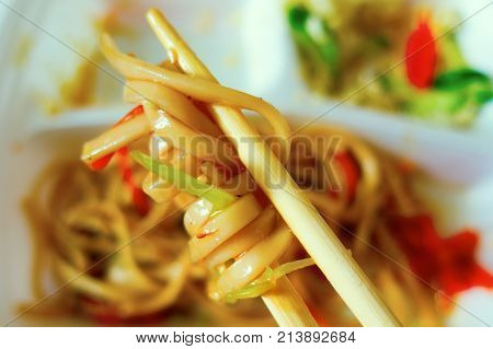 delicious and satiated Asian noodles on wooden sticks