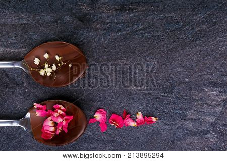 Two spoons with frozen chocolate in which lies petals of flowers