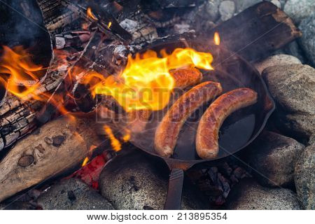 Cooking Sausages In Cast Iron Skillet On Campfire While Camping. Good And Positive Campfire Food.