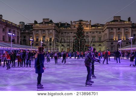 London UK - December 29. 2016: Skaters having fun at Somerset House at dusk. Evening shot with Christmas tree in the centre.