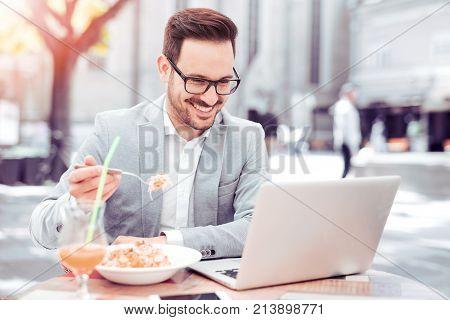 Businessman having a lunch break ,he is eating fresh pasta.