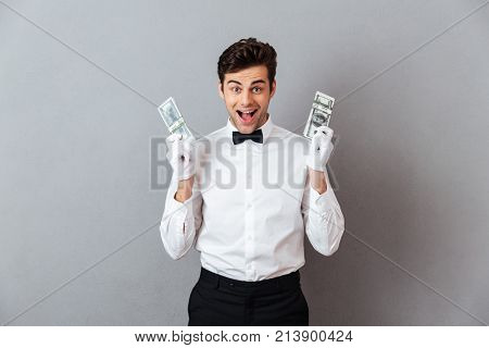 Portrait of a happy successful male waiter dressed in unifrom giving bunch of money banknotes isolated over gray background