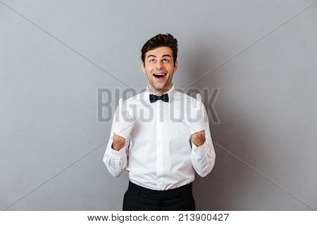 Portrait of a happy cheerful male waiter dressed in unifrom pointing two fingers up at copy space isolated over gray background