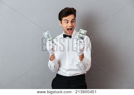 Portrait of a happy excited male waiter dressed in unifrom holding bunch of money banknotes isolated over gray background