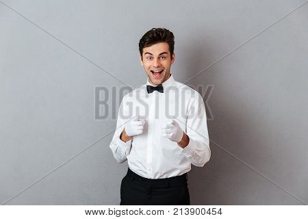 Portrait of a cheerful young male waiter dressed in unifrom pointing two fingers up at camera isolated over gray background