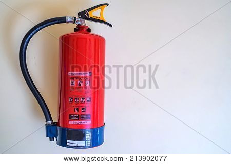 Close-up of red modern fire extinguisher in office