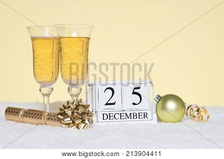 Christmas party still life with two glasses of Champagne and a date block showing 25th December. Copy space on the background for your own message such as invitation.