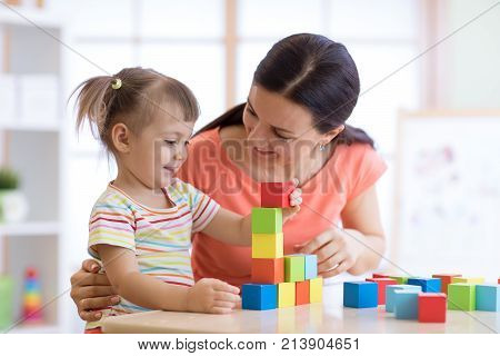 Cute woman and kid girl playing educational toys at kindergarten or nursery room