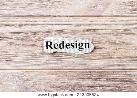 REDESIGN of the word on paper. concept. Words of REDESIGN on a wooden background.