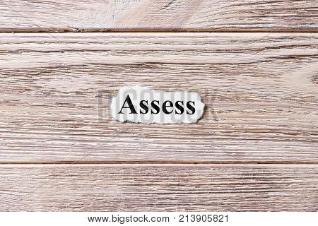 ASSESS of the word on paper. concept. Words of ASSESS on a wooden background.