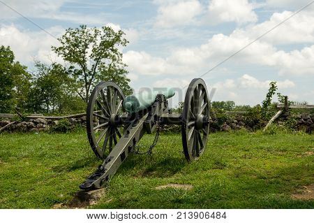Historic Cannon Artillery Pointing Over Stone Wall