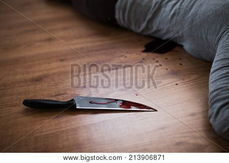 murder, kill and people concept - knife in blood lying on floor near dead woman body at at crime scene