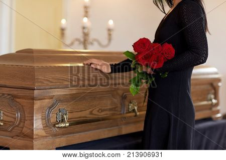burial, people and mourning concept - unhappy woman with red roses and coffin at funeral in church