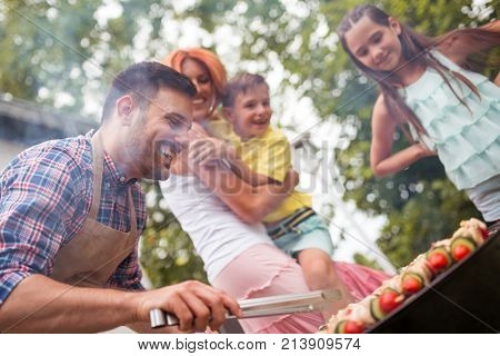 Leisure food people and holidays concept-man cooking meat on barbecue grill for his family at summer outdoor party.