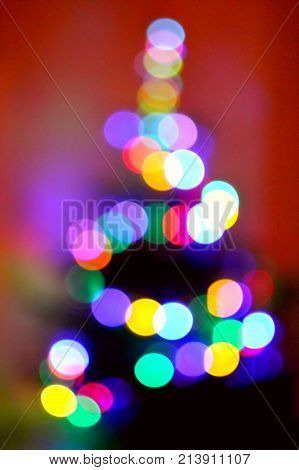 Red, orange, violet and green holiday bokeh. Abstract Christmas tree background.