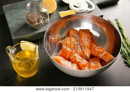 Metal bowl with marinated salmon on table