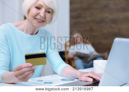 Bank operations. Positive smart responsible pensioner learning how to do bank operations with a new credit card