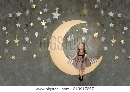 Little Girl In Sitting On Big Moon. Little Girl Dreaming