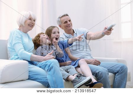Laughing relatives. Energetic positive cheerful relatives sitting together on a sofa and laughing