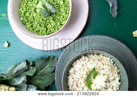 Cauliflower Rice And Broccoli Rice In Bowl On Green Background. Top View. Overhead. Copy Space. Shre