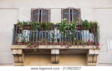 Rome Italy . Beautiful balcony and windows decorated with flowers .