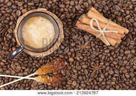 Strong fragrant cooked coffee with foam. A coffee drink in a cup. A cup of coffee, sugar stick and coffee pot on coffee beans. Freshly brewed coffee in a pot. Cinnamon near the cup with coffee and cezve top view