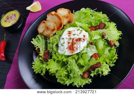 A Traditional Lyonnaise Salad On Black Plate