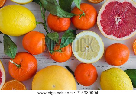Mixed citrus background. Assorted fresh citrus fruits with leaves on white wooden table. Lemon grapefruit mandarin. Harvest concept. Healthy eating dieting. Top view.