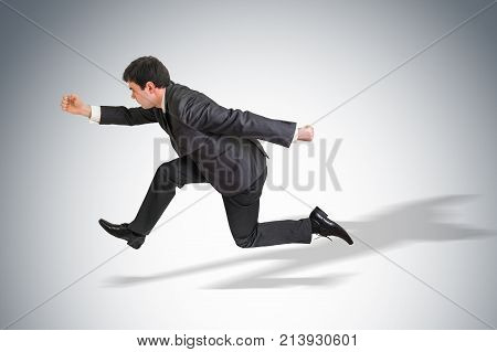 Small businessman with suit running away from a boss pressure