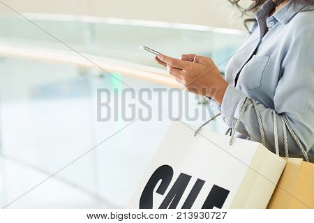 Hands of young woman with shopping bags texting to friend