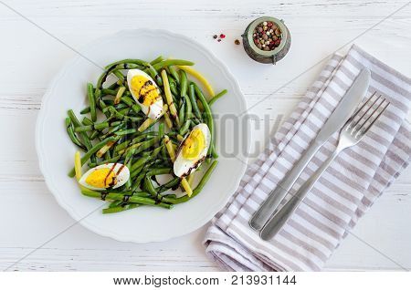 Fresh summer warm salad with cooked green beans with boiled eggs and sauce balsamico glassa in white plate on wooden background. Healthy eating. Vegetarian food concept. Top view.