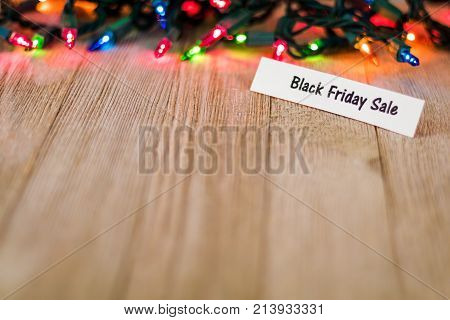 Black Friday Sale Concept on wooden board and colored lights, selective focus, room for copy