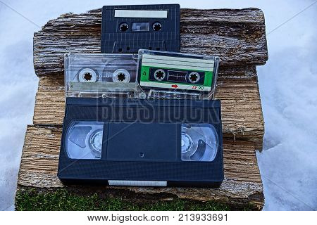 audio cassettes and video cassettes on wooden logs in the snow