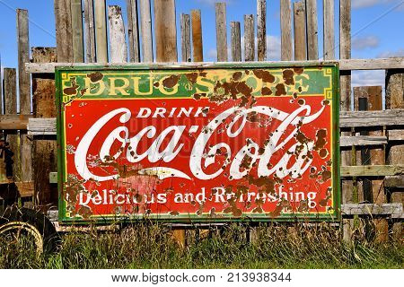 DOWNER, MINNESOTA, October 3, 2017: The old Coca Cola sign displayed on a fence advertises the soft drink invented by John Pemberton in the late 1800`s is headquartered in Atlanta, GA.