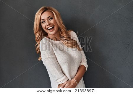 Always in good mood. Attractive young woman looking away and laughing while standing against grey background