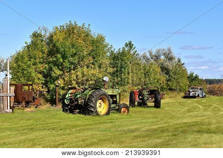 DOWNER, MINNESOTA, Oct 3, 2017:  The old John Deer R tractor parked in a field is a product of John Deere Co, an American corporation that manufactures agricultural, construction, forestry machinery, diesel engines, and drivetrains
