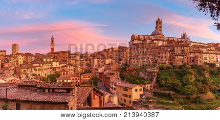 Beautiful panoramic view of Old Town with Dome and campanile of Siena Cathedral, Duomo di Siena, and Mangia Tower or Torre del Mangia at gorgeous sunset, Siena, Tuscany, Italy