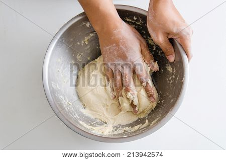 Bread cooking, kneading bread dough in a bowl by hand
