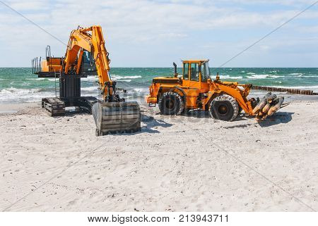 a wheel loader and an excavator on the beach