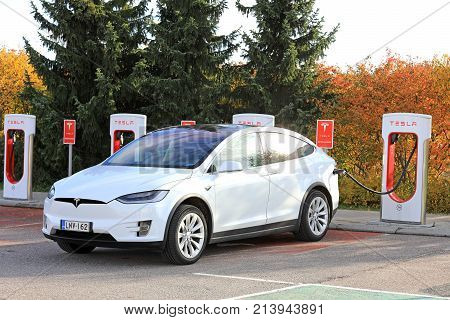 PAIMIO FINLAND - OCTOBER 15 2017: White Tesla Model X electric crossover SUV charges battery at Tesla Supercharger station in Paimio.