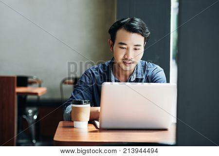 Young Asian man sitting in coffeeshop table and working on laptop