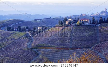 Autumnal panorama of the hilly region of Langhe (Piedmont, Northern Italy), a farm over the vineyards; world famous for its valuable red wines (Barolo and Barbaresco first), Langhe Monferrato and Roero are UNESCO World Heritage Site since 2013.