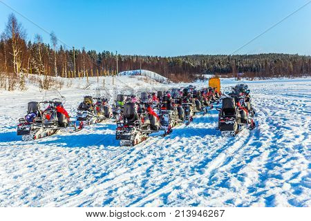 Tourist train from snowmobiles moves along the ice of a frozen river. Snowmobiling. Concept of active winter tourism