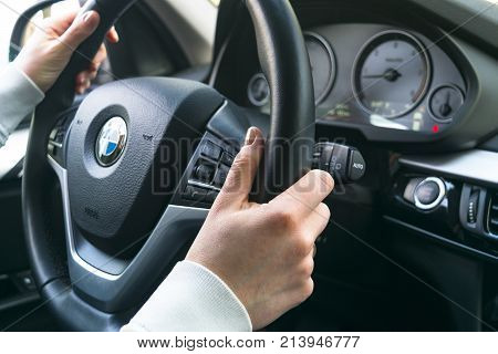 Sankt-Petersburg Russia November 16 2017: Woman's hands on a steering wheel driving BMW X5 F15. Hands holding steering wheel. Modern Car interior details.