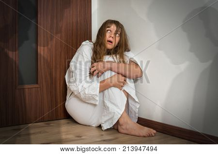 Scared woman with schizophrenia sitting in the corner at room with people shadows - hallucinations and schizophrenia disease concept