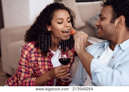 Black man and woman are sitting on the couch. A man and a woman embraced and drank wine and eat strawberries. They are happy. They rest after a hard day's work.
