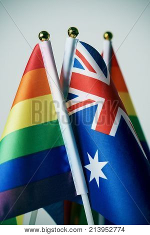 closeup of an australian flag and some rainbow flags, against an off-white background