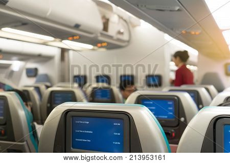 Beautiful air hostess or fight attendant waiting for service passengers on board in interior aircraft. Fight attendant with map time on monitor.