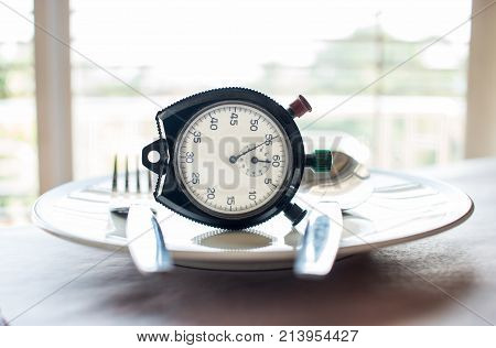Retro stopwatch to put on plate. Weight loss for good Healthy. Diet is sum of food consumed by person or other organism. Time to diet concept.