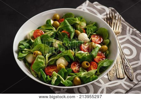 Salad with tomatoes, mozarella and olives .